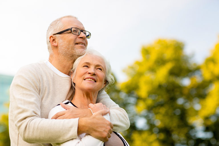 family age travel and people concept - senior couple hugging in park